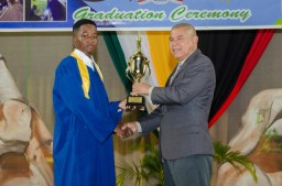 Minister of Social Cohesion, Hon. Dr. George Norton presents trophy to Best Graduating Student, Isaiah Knights at the National Cultural Center.