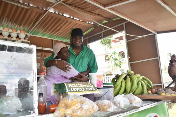 Director-General of the Ministry of the Presidency, Joseph Harmon in with a vendor in Plaisance.