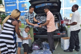 His Worship the Mayor of Georgetown, Pandit Ubraj Narine and Councilor Eon Bollers distribute school supplies on Thursday to more than 100 children at the Alberttown Recreational Park.