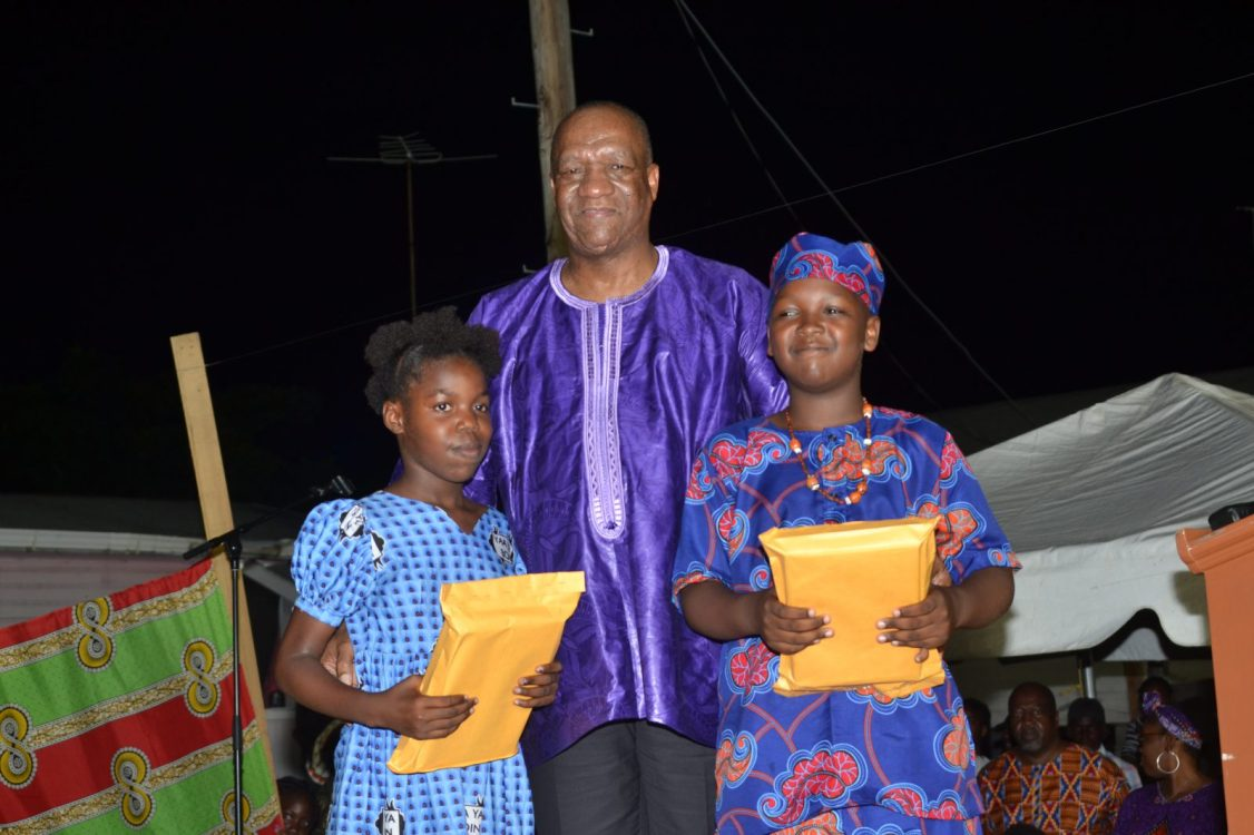 Director-General (DG) of the Ministry of the Presidency, Joseph Harmon, along with two students of Buxton Village after handing over their electronic tablet