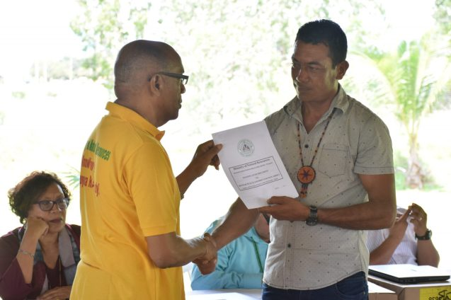 Project Coordinator of FCPF-REDD+ Guyana, Clayton Hall, hands over a REDD+ Guyana package to SRDC's Chairman Nicholas Fredericks