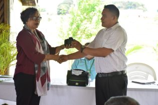 Minister within the Ministry of Indigenous Peoples Affairs, Valerie Garrido-Lowe hands over a REDD+ Guyana package to KMCRG's President and Toshao of Yupukari Russian Dorrick