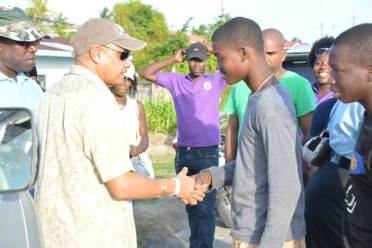 Minister of Business, Hon. Haimraj Rajkumar greeting one of the young men during the walkabout in the Golden Fleece community.