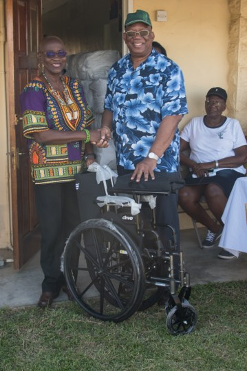 Minister Jordan hands over one of two wheelchairs to Member of Parliament, Hon. Jennifer Wade