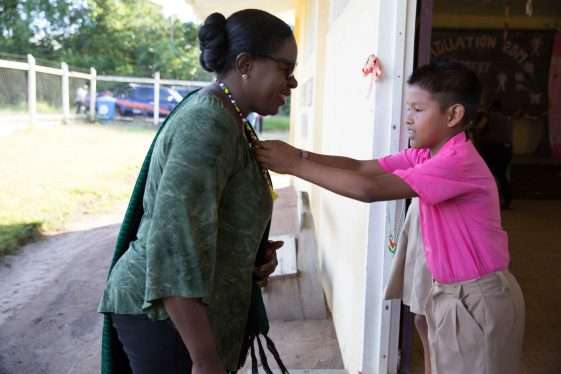 Minister of Education, Hon. Dr. Nicolette Henry is being greeted by a student of the El Paso Primary, Region 8 following the government's outreach held in the region on Friday