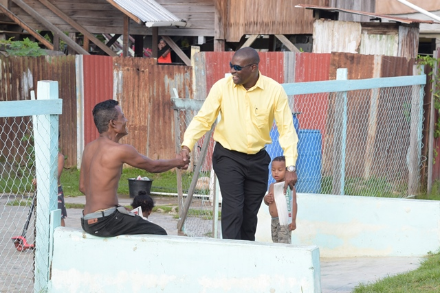 Minister of Public Infrastructure Hon. David Patterson greets a resident of Rose Hall during a walkabout in the township