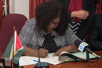 Minister of Foreign Affairs, Hon. Dr. Karen Cummings signing the revised Supplementary Agreement of the IAEA.