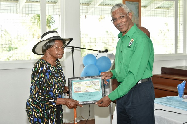 President David Granger, this afternoon, received from Mrs. Evelyn Bacchus, the oldest resident of Victoria Village, the Village's 177th anniversary commemorate stamp.