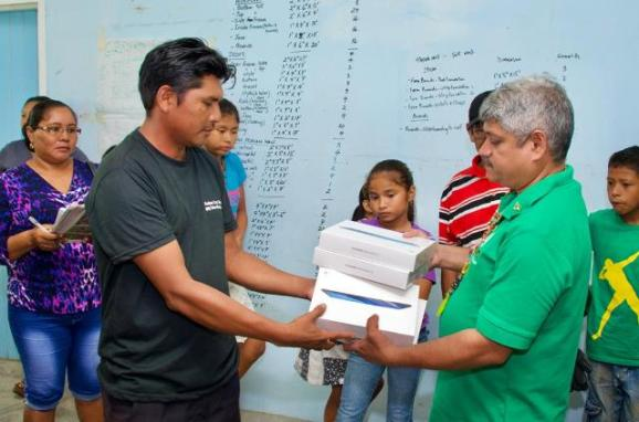 Minister Sharma hands over electronic tablets to the community.