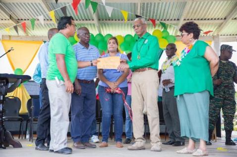 President David Granger handing over a cheque to Toshao of Sebai, Vincent Emanuel in the presence of Minister of Social Protection, Hon. Amna Ally.