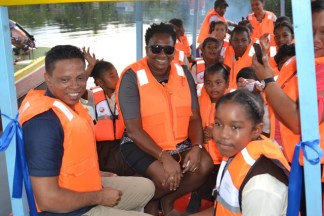 Minister within the Ministry of Communities, with responsibility for Housing, Hon. Annette Ferguson joins the students of Dora Primary School for a test ride on the new boat.