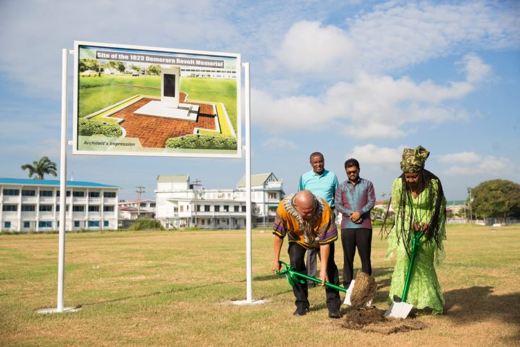 Minister of Social Cohesion, Hon. Dr. George Norton and President of the 1823 Coalition for the Parade Ground Movement, Sister Penda Guyan, turn the sod for the new 1823 Demerara Slave Revolt Monument, as His Worship Ubraj Narine and Deputy Mayor Alfred Mentore look on
