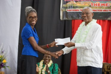 His Excellency, President David Granger hands over the cheque to Headteacher of New Amsterdam Multilateral School, Vanessa Jacobs.