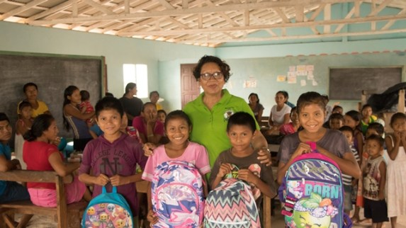 Some children in all smiles as they receive school bags and supplies from Minister within the Ministry of Indigenous Peoples' Affairs, Valerie Garrido- Lowe.