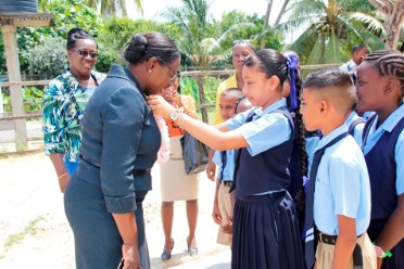 A student of Cotton Tree Primary School greeting the Minister of Education