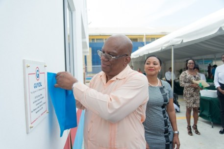 Minister of Finance, Hon. Winston Jordan unveils the plaque to commission the GUYOIL green store and complex .