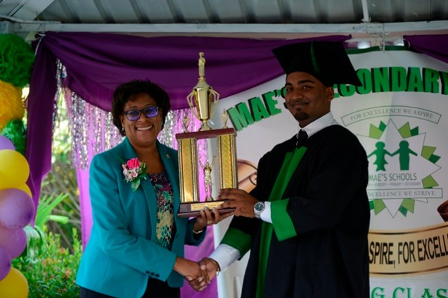 Minister of Public Telecommunications, Hon. Minister Catherine Hughes hands over trophy to Damian Seeraj, who graduated top of the class at Mae's Secondary, securing 13 Grade ones at the Caribbean Secondary Education Certificate (CSEC).