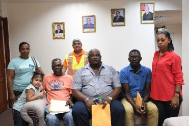Minister Jaipaul Sharma behind in the reflector's vest poses (from left) Mr. Mark Smith, Mr. Roger Anderson, and Mr. Curtley Charles; the three Boat Operators who shared their concerns with Minster Sharma.