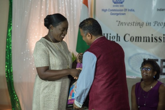 Minister of Education, Hon. Dr. Nicolette Henry receiving a token from High Commissioner of India to Guyana, His Excellency Dr. K. J. Srinivasa.