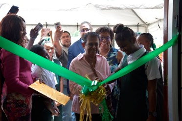 Former Director of the Anna Regina Post Office, Sabra Basir, along with a student from the Anna Regina Multilateral Secondary, cuts the ribbon to commission the Post Office while Minister of Public Telecommunications, Hon. Catherine Hughes looks on.