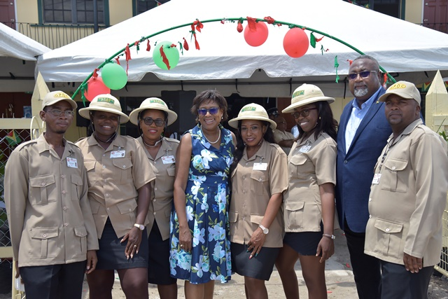 Minister of Public Telecommunications, Hon. Catherine Hughes and Chairman of Board of Directors at GPOC, Reverend Dr. Murtland Massiah share a light moment with some Postmen and Postwomen.