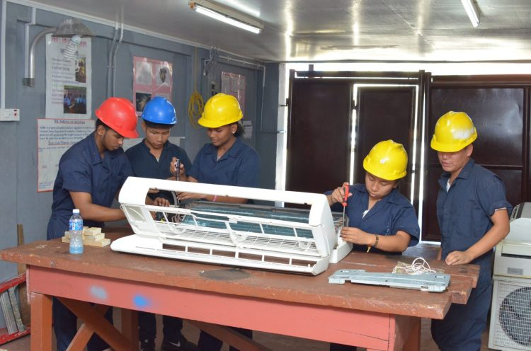 Some of the students attached to the Essequibo Technical Institute (ETI) repairing an air conditioner.