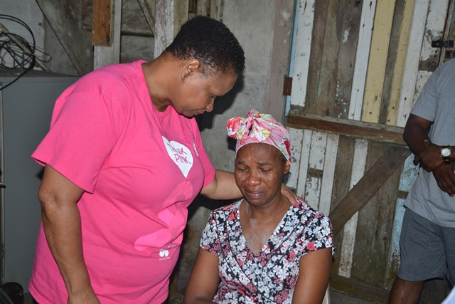 Minister Lawrence consoles mother of Nurse Reddock, Merelene Niles at her Amelia's Ward home.