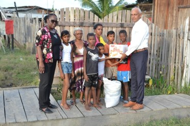 Minister of Communities, Hon. Ronald Bulkan handing over are packages to an affected family.