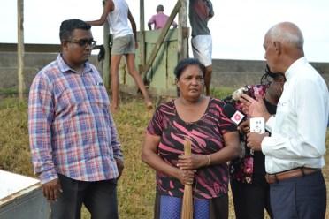 Minister of Communities, Hon. Ronald Bulkan and Regional Information Officer, Ganesh Mahipaul engaging an affected resident.