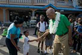 His Excellency, President David Granger greets a little boy who came out to meet him accompanied by his mother.