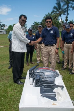 Minister of Public Security K Khemraj hands over the boat engine to member of the White Water CPG Orbin Domingo
