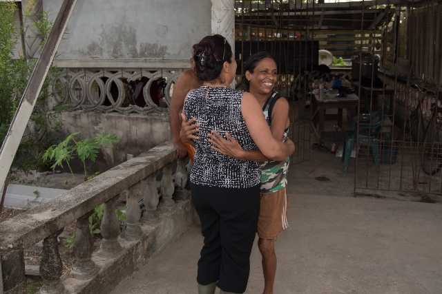 Flood affected resident, Fareeda Nabbi happily welcomes Minister of State, Hon. Dawn Hastings-Williams, during the distribution of hampers.
