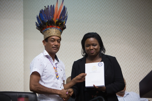 Office of the Prime Minister, Coordinator of the Department of Governance, Tamara Khan officially hands over a copy of the Constution of Guyana to Chairman of the National Toshaos Council, Toshao Nicholas Fredericks.