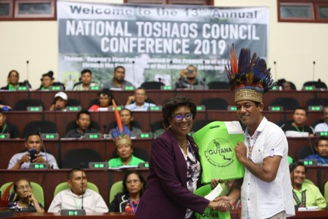 Minister of Public Telecommunications, Hon. Catherine Hughes presents Chairman of the NTC and Toshao of Shulinab, Nicholas Fredericks with his electronic tablet.