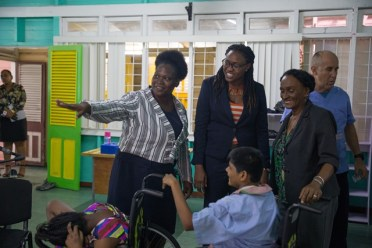 Minister of Public Service, Hon. Tabitha Sarabo-Halley interacting with one of the students in the presence of the staff of the complex.