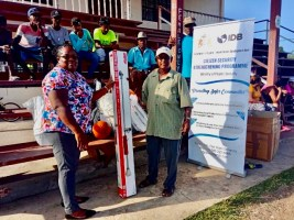 Community Action Officer Arjuna Veersammy of Kilcoy/Chesney receives the sports gear in the presence of youth beneficiaries.