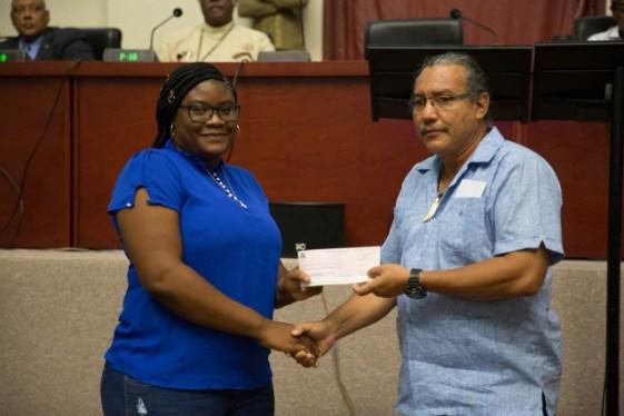 Ministerial Advisor and Member of Parliament (MP), Hon. Mervyn Williams handing over a cheque to Arakaka.