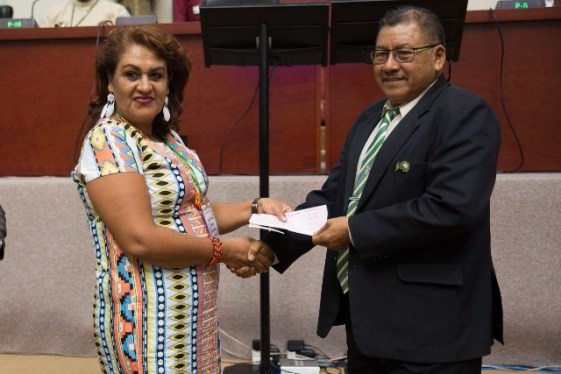 Toshao of Santa Rosa, Whanita Phillips receiving a cheque from Minister of Indigenous Peoples' Affairs, Hon. Sydney Allicock.