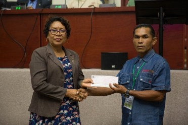 Toshao of Hotoqual, Owen Singh receiving a cheque from Minister within the Ministry of Indigenous Peoples' Affairs, Hon. Valerie Garrido-Lowe.