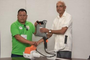 Minister of Communities, Hon. Ronald Bulkan handing over the brush cutter to Senior Councillor of Karasabai, Carlos Francis.