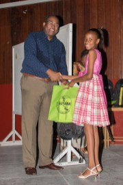 Mentor and Attorney-at-Law, Nigel Hughes hands over the award and gift to one of the mentees.