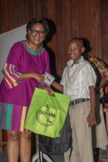 Minister of Public Telecommunications, Hon. Catherine Hughes hands over the award and gift to one of the mentees.