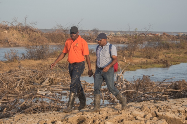 Minister of Public Infrastructure, Hon. David Patterson inspects the damage to the earthen embankment in Mahaicony with the Chief Sea and Rive Defence Officer within the Public Infrastructure Ministry, Kevin Samad.