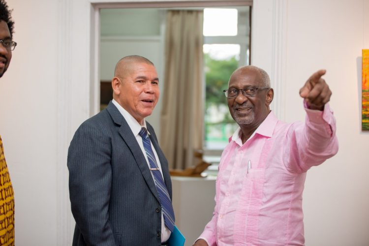 Minister of Social Cohesion, Hon. Dr. George Norton and Ministry of within the Ministry of Social Protection, Hon. Keith Scott [right], intrigued by the exhibits.