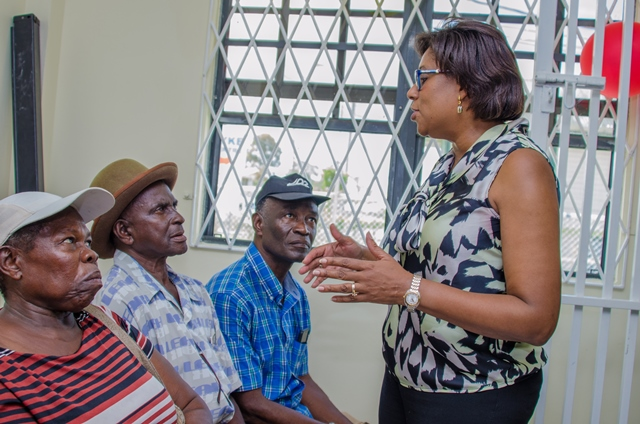 Minister of Public Telecommunications, Hon. Catherine Hughes interacts with senior folks as the sit patiently at the Post Office.
