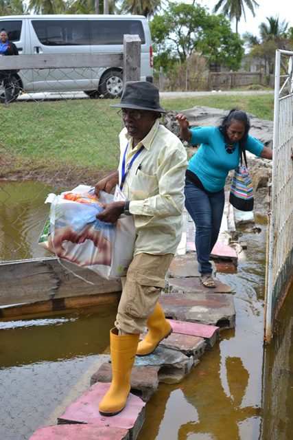 Councilor Cleveland Ramsammy assisting resident Annette Balgobin with her food hamper.