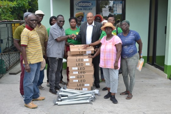 Minister of Natural Resources, Hon. Raphael Trotman handing over the LED lights and poles to Morris Wilson, flanked by other residents of the community.