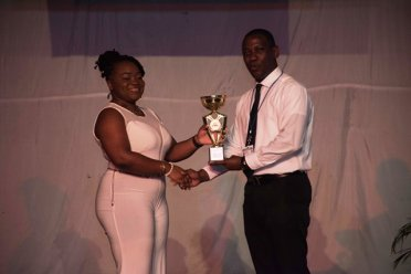 The best graduate, Omallia Thorington, receiving her trophy from BNTF Chairman Bernard Lord, of the latest Basic Needs Trust Fund and Merundoi audiovisual skills training project, at the Theater Guild Playhouse.