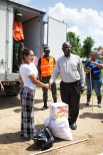 Minister of Citizenship, Hon. Winston Felix hands over a quantity of items to one of the residents in Golden Grove.