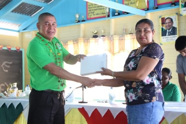 Minister of Social Cohesion, Hon. Dr. George Norton presents an electronic tablet to one of the Abrams Creek Primary School teachers.